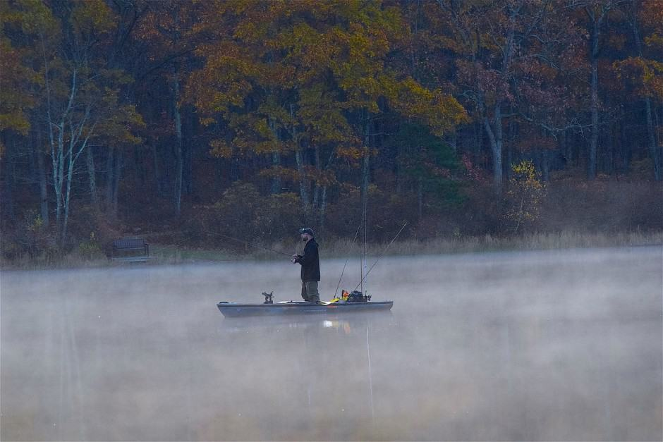 dawn boat fishing in the morning mist